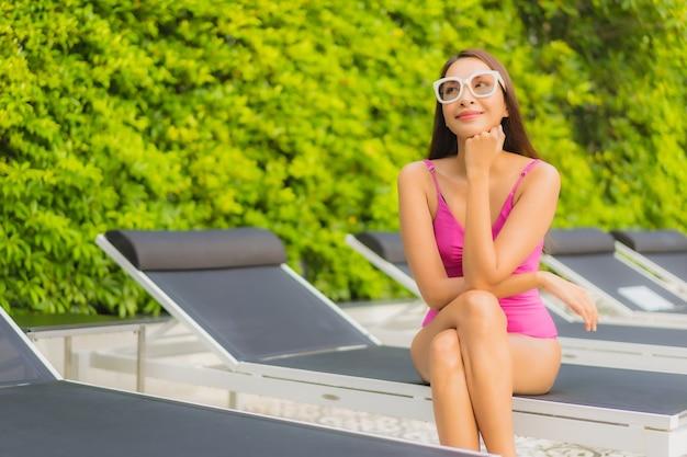 초상화 아름 다운 젊은 아시아 여자는 호텔 리조트에서 야외 수영장 주위에 미소를 긴장