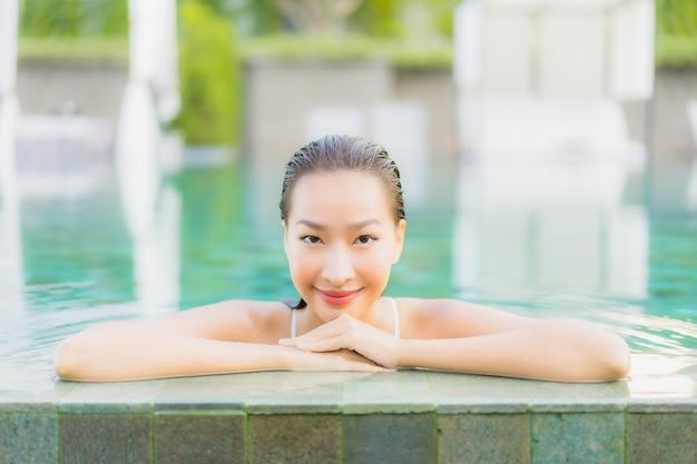 Женщина портрета красивая молодая азиатская ослабляет улыбку вокруг открытого бассейна в курорте гостиницы