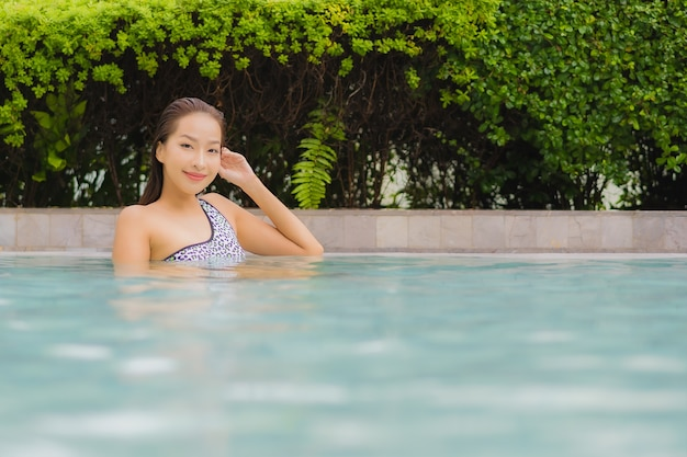 Portrait beautiful young asian woman relax smile around outdoor swimming pool for leisure and vacation