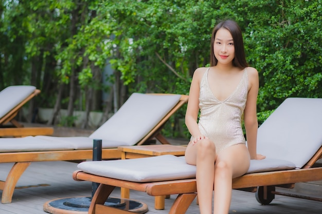 Женщина портрета красивая молодая азиатская ослабляет улыбку вокруг открытого бассейна
