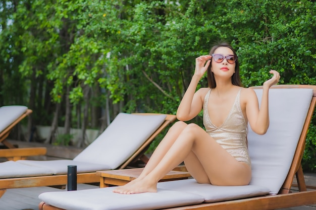 Portrait beautiful young asian woman relax smile around outdoor swimming pool