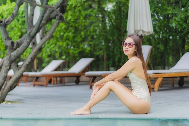 肖像画の美しい若いアジア女性は屋外スイミングプールの周りの笑顔をリラックスします。