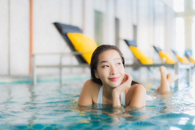 Portrait beautiful young asian woman relax smile around swimming pool in hotel resort on traval vacation