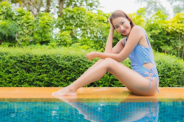 La bella giovane donna asiatica del ritratto si rilassa il sorriso intorno alla piscina nella località di soggiorno dell'hotel per le vacanze di viaggio