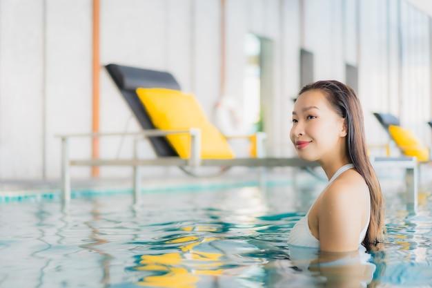 肖像画の美しい若いアジアの女性は、traval休暇でホテルリゾートのスイミングプールの周りの笑顔をリラックスします。