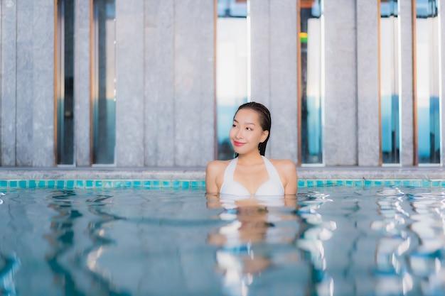 Женщина портрета красивая молодая азиатская ослабляет улыбку вокруг бассейна в курорте гостиницы на каникулах traval