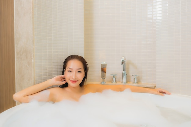 Portrait beautiful young asian woman relax smile in bathtub at bathroom interior