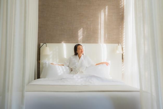 La bella giovane donna asiatica del ritratto si rilassa il sorriso sul letto in camera da letto
