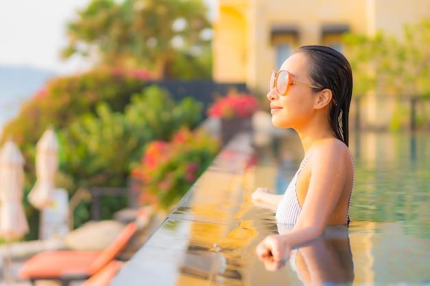 Женщина портрета красивая молодая азиатская ослабляет улыбку наслаждается отдыхом вокруг бассейна в курортном отеле на каникулах