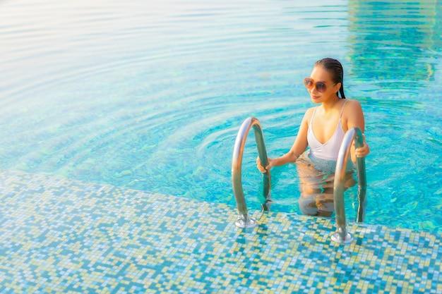 肖像画美しい若いアジアの女性は笑顔をリラックスして休暇でリゾートホテルのプールの周りのレジャーをお楽しみください