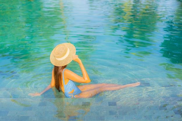 Женщина портрета красивая молодая азиатская ослабляет улыбку наслаждается отдыхом вокруг плавательного бассейна почти с видом на океан пляжа моря на каникулах
