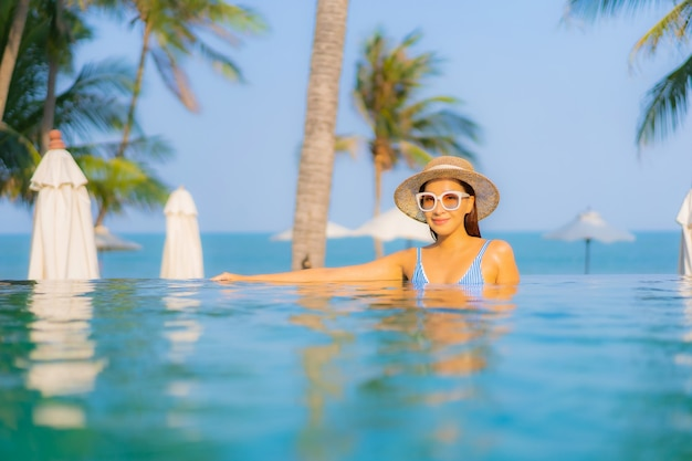 肖像画美しい若いアジアの女性は笑顔をリラックスしてスイミングプールの周りのレジャーをお楽しみください