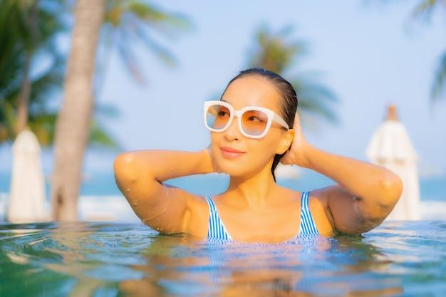 La bella giovane donna asiatica del ritratto si rilassa il sorriso gode di svago intorno alla vista sull'oceano della spiaggia del mare quasi della piscina in vacanza