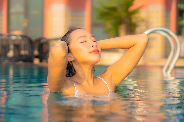 Portrait beautiful young asian woman relax smile enjoy leisure around swimming pool in resort hotel on vacation