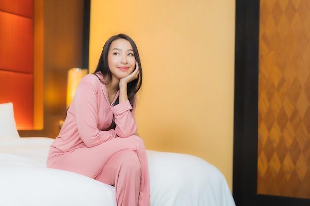 肖像画の美しい若いアジア女性は寝室のインテリアのベッドで幸せな笑顔をリラックス