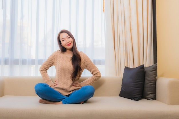 肖像画の美しい若いアジア女性は寝室のソファ装飾インテリアで幸せな笑顔をリラックス