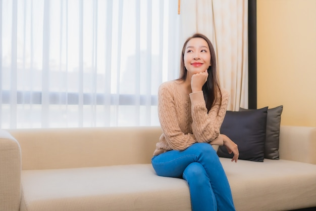 Portrait beautiful young asian woman relax smile happy on sofa decoration interior of bedroom