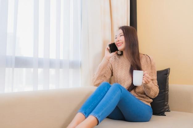 肖像画の美しい若いアジアの女性はソファーでコーヒーを飲みながらスマートフォンに満足して笑顔をリラックスします。