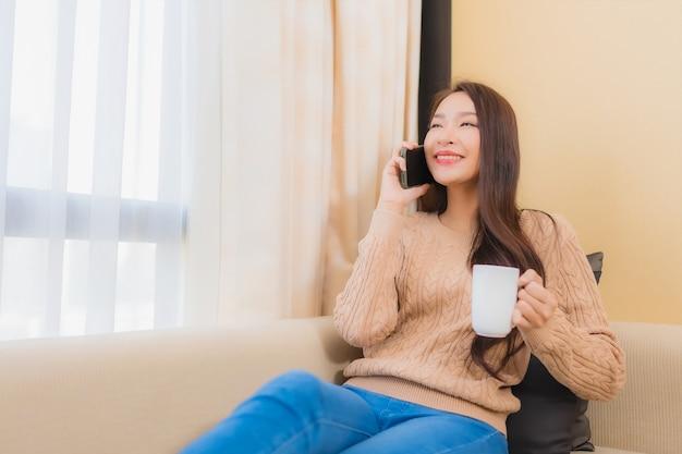 La bella giovane donna asiatica del ritratto si rilassa il sorriso felice con lo smart phone con il caffè sul sofà