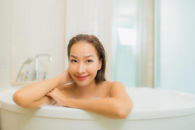 肖像画の美しい若いアジア女性はバスルームのインテリアでバスタブで笑顔をリラックスします。