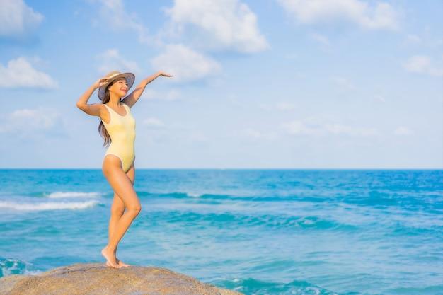 Женщина портрета красивая молодая азиатская ослабляет отдых улыбки вокруг океана моря пляжа на поездке каникул