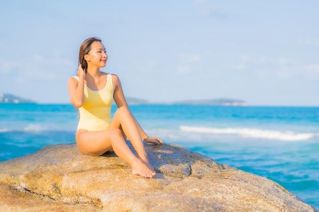 초상화 아름 다운 젊은 아시아 여자는 여행 휴가 여행에 해변 바다 바다 주위에 미소 레저 휴식