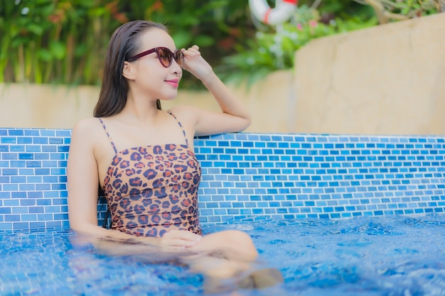 Portrait beautiful young asian woman relax smile leisure around outdoor swimming pool in holiday vacation travel trips