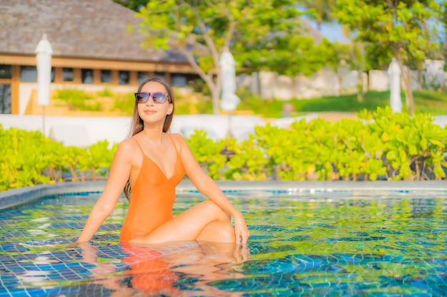 Portrait beautiful young asian woman relax smile leisure around outdoor swimming pool in hotel resort on travel vacation