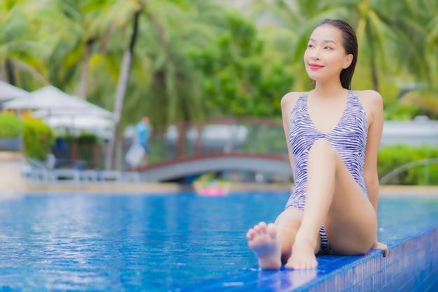 La bella giovane donna asiatica del ritratto si rilassa il tempo libero di sorriso intorno alla piscina all'aperto nella località di soggiorno dell'hotel sul viaggio di vacanza