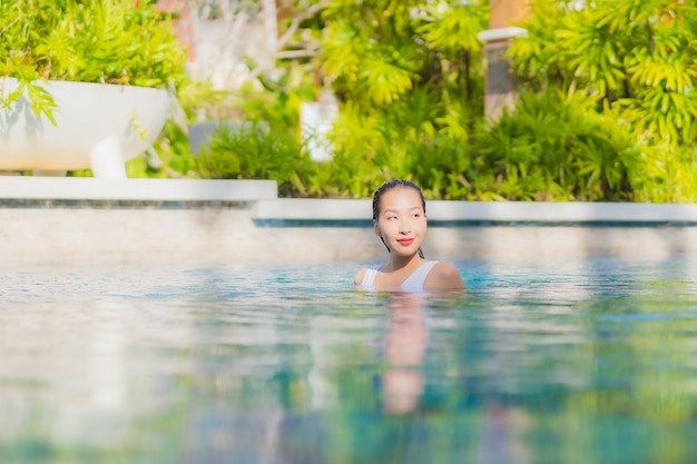 Portrait beautiful young asian woman relax smile leisure around outdoor swimming pool in hotel resort on vacation travel