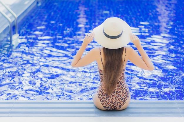 Женщина портрета красивая молодая азиатская ослабляет отдых улыбки вокруг открытого бассейна в поездках каникул праздника