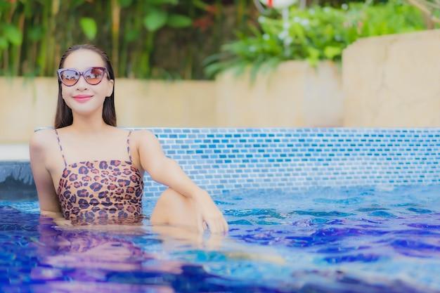 肖像画美しい若いアジアの女性は、休日の休暇旅行旅行で屋外スイミングプールの周りの笑顔のレジャーをリラックス