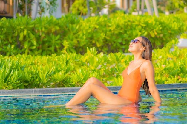肖像画美しい若いアジアの女性は旅行休暇でホテルリゾートの屋外スイミングプールの周りの笑顔のレジャーをリラックス 無料写真