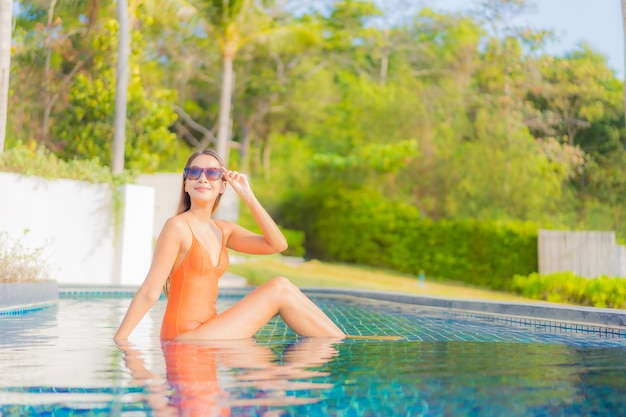 肖像画美しい若いアジアの女性は旅行休暇でホテルリゾートの屋外スイミングプールの周りの笑顔のレジャーをリラックス