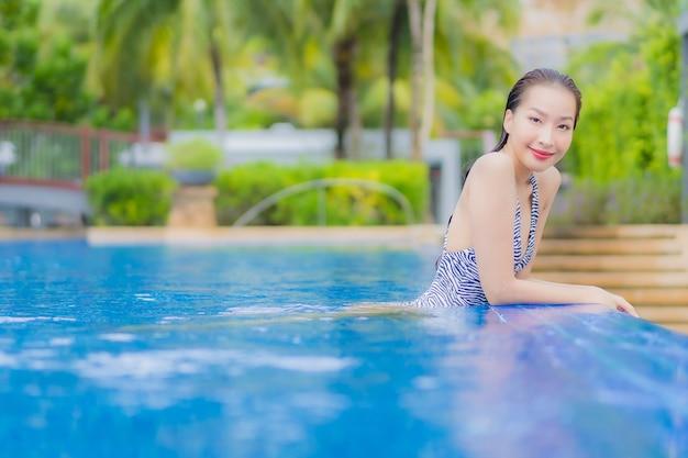 肖像画美しい若いアジアの女性は休暇旅行でホテルリゾートの屋外スイミングプールの周りの笑顔のレジャーをリラックス