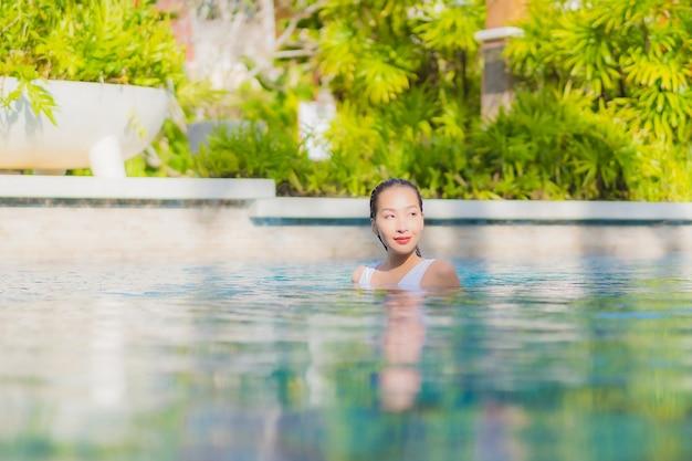 Женщина портрета красивая молодая азиатская ослабляет отдых улыбки вокруг открытого бассейна в курорте гостиницы на путешествии каникул
