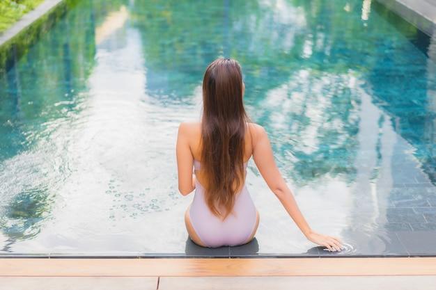 세로 아름 다운 젊은 아시아 여자 호텔 리조트에서 야외 수영장 주변 미소 레저 휴식