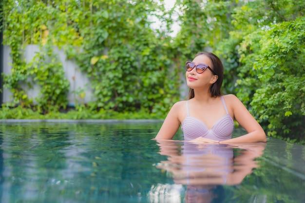 肖像画美しい若いアジアの女性がホテルリゾートの屋外スイミングプールの周りの笑顔のレジャーをリラックス