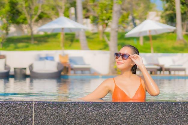 Женщина портрета красивая молодая азиатская ослабляет отдых улыбки вокруг открытого бассейна в курортном отеле с видом на океан моря