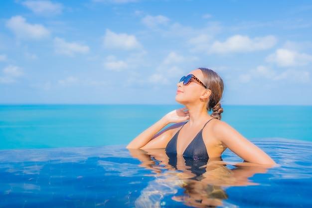 초상화 아름 다운 젊은 아시아 여자는 바다 바다 전망 리조트 호텔에서 야외 수영장 주변 미소 레저 휴식