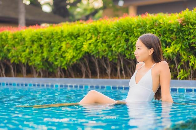 Женщина портрета красивая молодая азиатская ослабляет отдых улыбки вокруг открытого бассейна почти моря