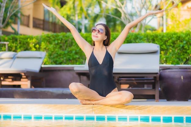 초상화 아름 다운 젊은 아시아 여자는 거의 바다에 가까운 야외 수영장 주변 미소 레저 휴식