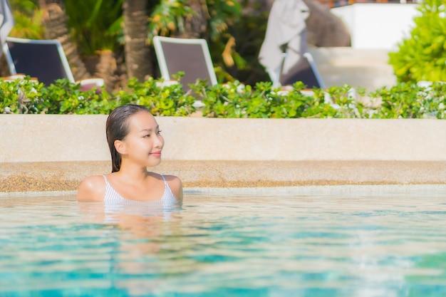 肖像画美しい若いアジアの女性は旅行休暇で海の海と屋外スイミングプールの周りの笑顔のレジャーをリラックス