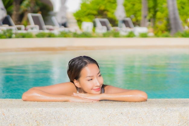Portrait beautiful young asian woman relax smile leisure around outdoor swimming pool with sea ocean in travel vacation