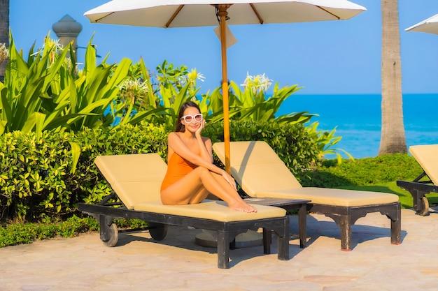 아름다운 젊은 아시아 여성의 초상화는 바다 전망이 있는 야외 수영장 주변에서 미소를 짓고 휴식을 취합니다.