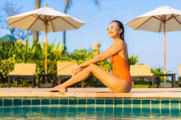 肖像画美しい若いアジアの女性は海の海の景色を望む屋外スイミングプールの周りの笑顔のレジャーをリラックス