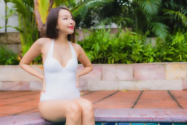 美しい若いアジアの女性の肖像画は屋外スイミングプールの周り笑顔レジャーをリラックスします。