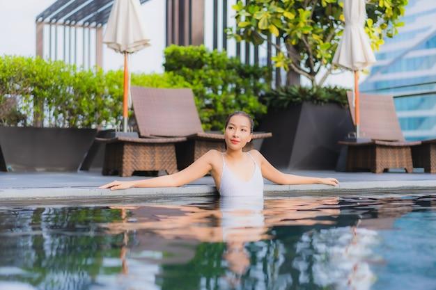 Женщина портрета красивая молодая азиатская ослабляет отдых улыбки вокруг открытого бассейна