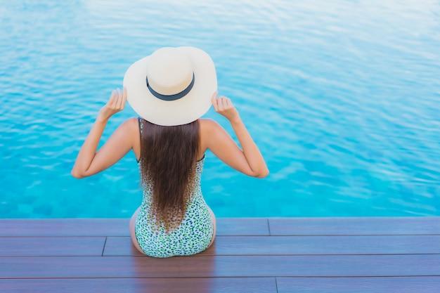 La bella giovane donna asiatica del ritratto si rilassa il tempo libero di sorriso intorno alla piscina all'aperto