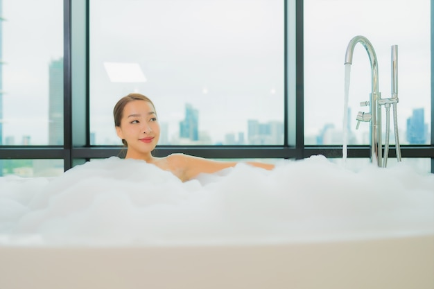 Portrait beautiful young asian woman relax smile leisure in bathtub in bathroom interior